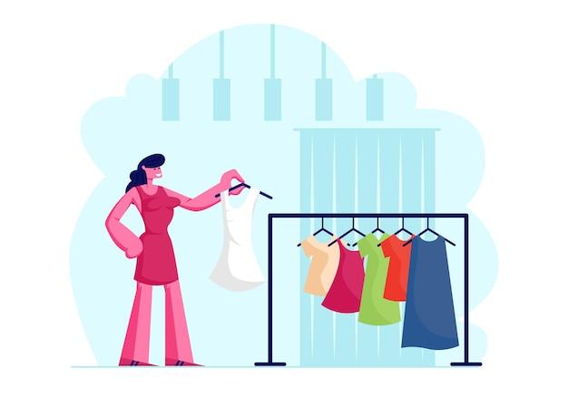 저장소에 새로운 구식 드레스를 선택하는 젊은 세련 된 여자
