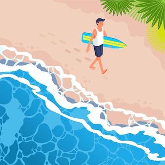 Молодой серфер гуляет по пляжу с доской для серферов