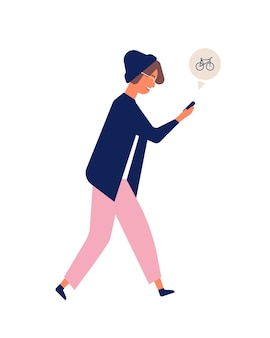 Young teenage man in hat using electronic gadget while walking