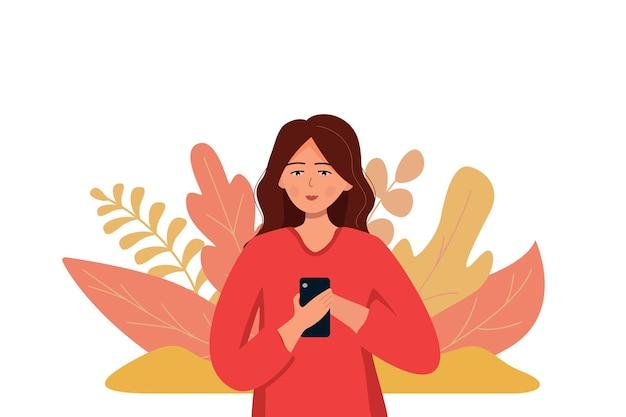 Молодая модная девушка стоит с телефоном в руках с природой и листьями. связь по телефону.