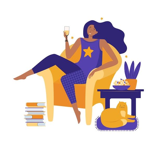 家にいる若い女性。大きな黄色い椅子に座ってワインを飲みながら快適に休んでいる快適なパジャマを着た女の子。