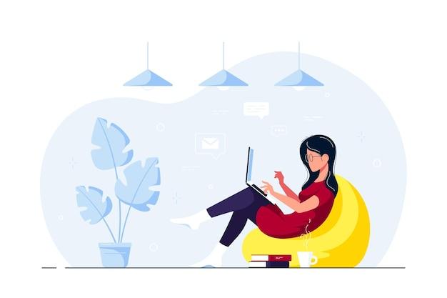 Молодая женщина дома сидит в кресле-мешке и работает на компьютере. удаленная работа, домашний офис, концепция самоизоляции. плоский стиль иллюстрации.