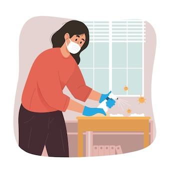 살균제 스프레이로 테이블을 청소하는 젊은 여자