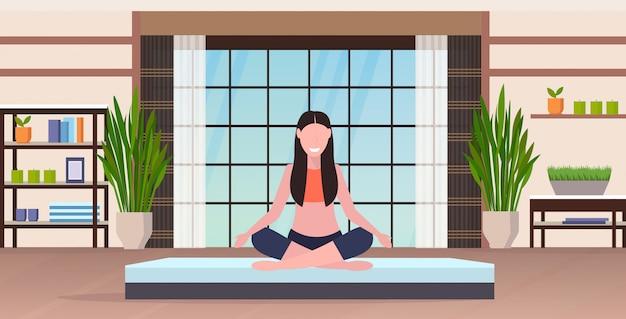 로터스 포즈 명상 휴식 개념 현대 체육관 인테리어 전체 길이 가로 앉아 스포츠 피트 니스 소녀 미소 요가 연습을 하 고 젊은 여자
