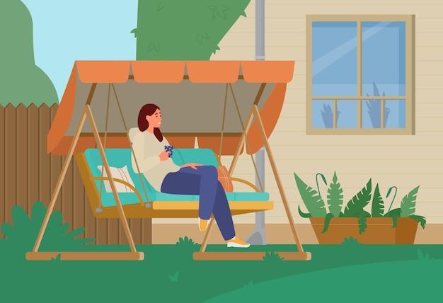 Молодая женщина пьет кофе и отдыхает в садовых качелях на заднем дворе