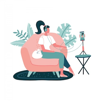 Young woman in headset recording podcasts, online training, music using smartphone on a tripod. girl sitting in armchair with cat at home on white background.   flat hand drawn illustration.
