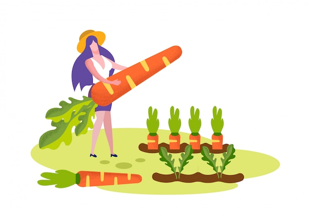 Young woman hold huge carrot stand on garden bed
