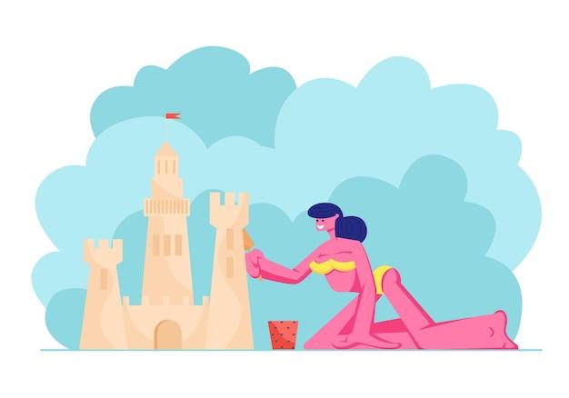 Молодая женщина в бикини развлекается на песчаном пляже, строя замок из песка на берегу тропического острова