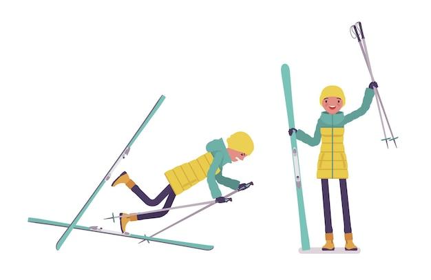 スキーを保持している明るいダウンジャケットの若い女性