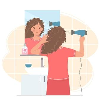 거울 앞에서 젊은 여자가 헤어 드라이어로 머리카락을 말립니다.