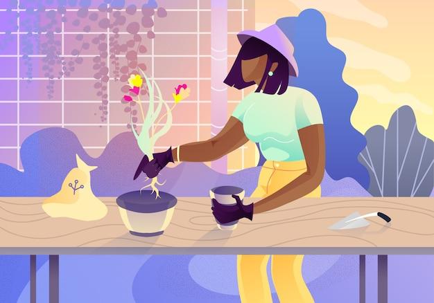 장갑과 꽃을 심는 모자에 젊은 여자.