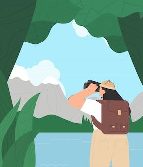 녹색 자연 배경에 쌍안경을 통해 찾고 옷을 하이킹에 젊은 여자.