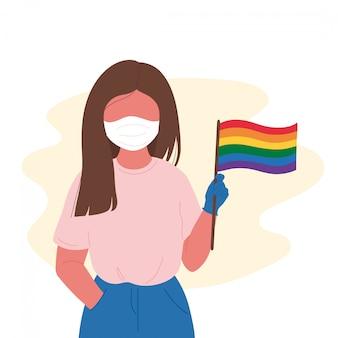 Молодая женщина в медицинской маске держит флаг лгбтк