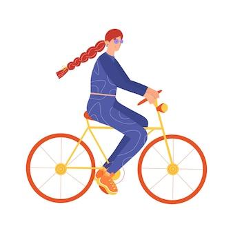 スポーツウェアの若い女性が自転車に乗る