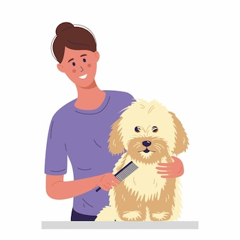 A young woman is combing a little dog with long fur taking care of grooming for pets