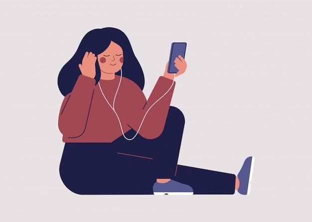 젊은 여자는 그녀의 스마트 폰에 헤드폰으로 음악 또는 오디오 북을 듣고있다.