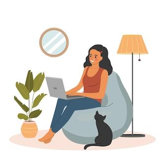 젊은 여성은 편안한 빈백 의자에서 휴식을 취하고 노트북을 사용하고 있습니다.