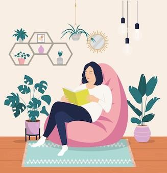 젊은 여자는 편안한 의자에 편안하고 책을 읽고