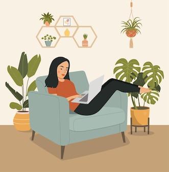 젊은 여자가 편안한 의자에 편안하고 노트북을 사용