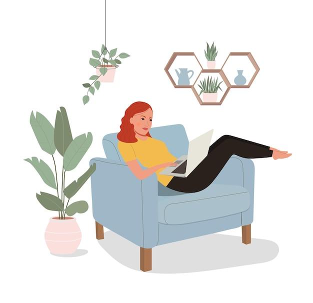 若い女性は快適な椅子とラップトップを使用してリラックスしています。