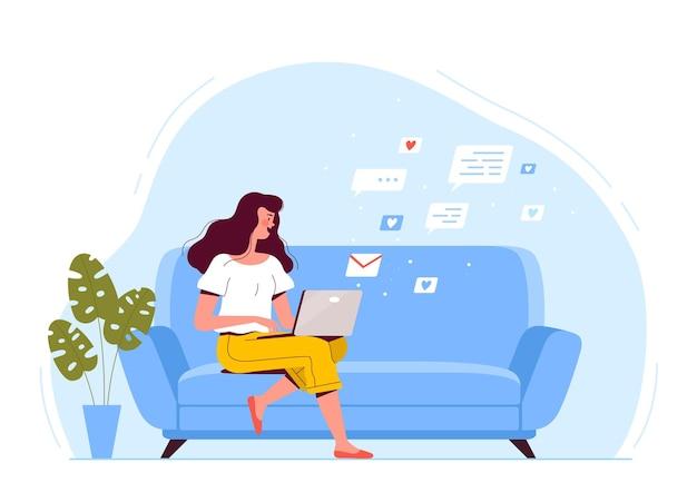 젊은 여자가 소파에 앉아 노트북을 들고 이메일로 문자 메시지를 보냅니다.