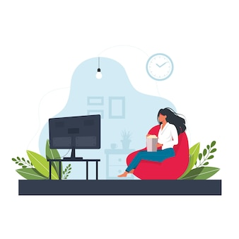 A young woman is sitting on the pouf, watching tv and eating popcorn. the concept of daily life, everyday leisure and work activities. flat cartoon vector illustration.