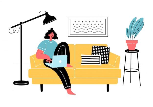 若い女性はラップトップで快適なソファに座っています。フリーランス、オンライン教育、ソーシャルメディアのコンセプト。隔離、自己分離。