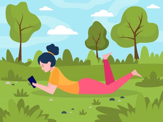 スマートフォンで草原に横たわっている若い女性