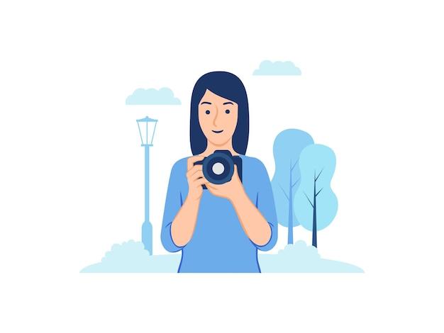 Молодая женщина-фотограф держит камеру, фотографирующую на открытом воздухе в парке, иллюстрации концепции
