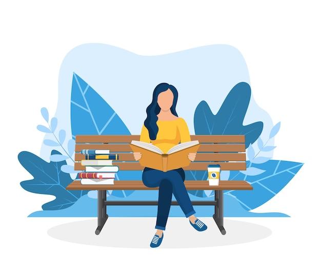 ベンチで本を読んでいる若い女性。