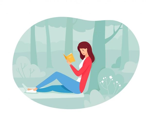 森の木の下で紙の本を読んで若い女性