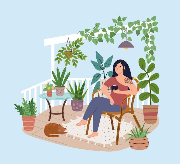 テラスの快適な椅子でリラックスした若い女性。バルコニーでコーヒーを飲む女の子