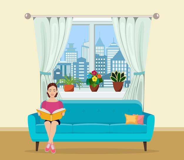 집에서 소파에 앉아 책을 읽는 젊은 여성
