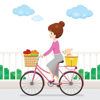 Young woman riding bicycle with fruits in front basket and dog sitting behind