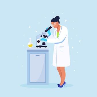 化学研究、微生物学的分析または医学的検査を行う実験室で顕微鏡を通して見ている若い女性の科学者