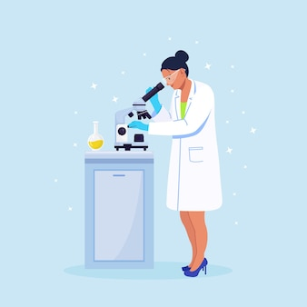 Young woman scientist looking through a microscope in a laboratory doing chemical research, microbiological analysis or medical test