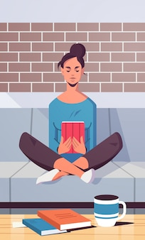 Young woman sitting on couch using tablet girl reading e-book e-learning concept modern