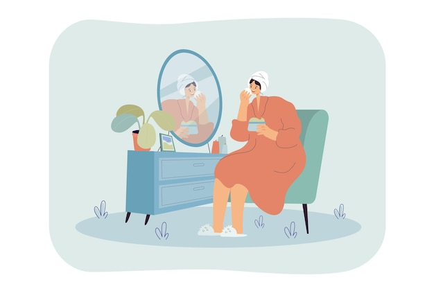 Young woman sitting in front of mirror and washing, cleansing or moisturizing her face skin in morning.