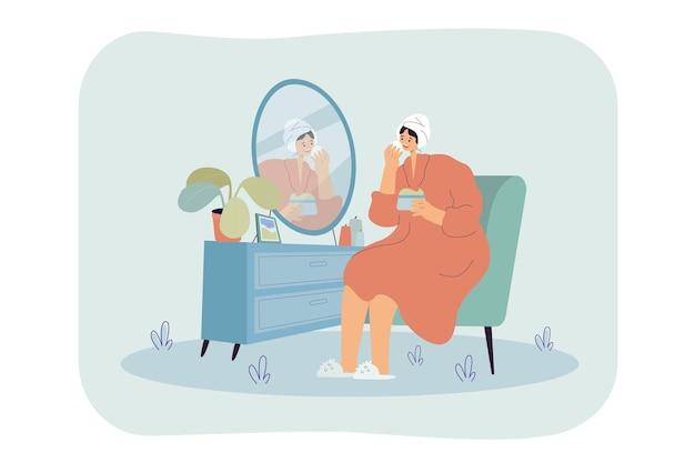 Молодая женщина сидит перед зеркалом и утром умывает, очищает или увлажняет кожу лица.