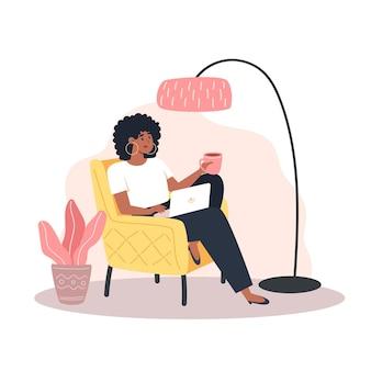안락의자에 앉아 집에서 노트북 작업을 하는 젊은 여성