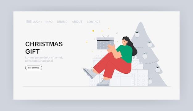 Молодая женщина, сидя на подарочной коробке, на фоне рождественской елки.