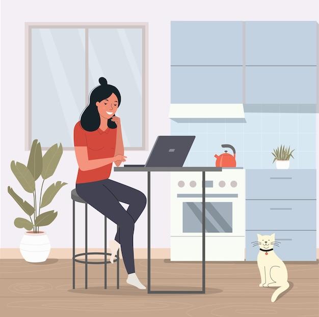 자에 앉아서 부엌에서 노트북으로 작업하는 젊은 여자.