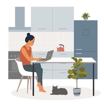 椅子に座って、キッチンでノートパソコンで作業している若い女性。