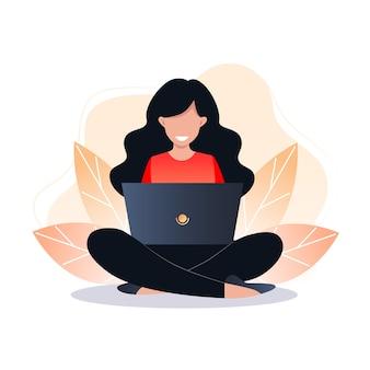젊은 여자는 바닥에 앉아 노트북에서 작업