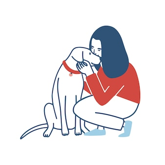 Young woman squatted down, hugs and kisses her dog