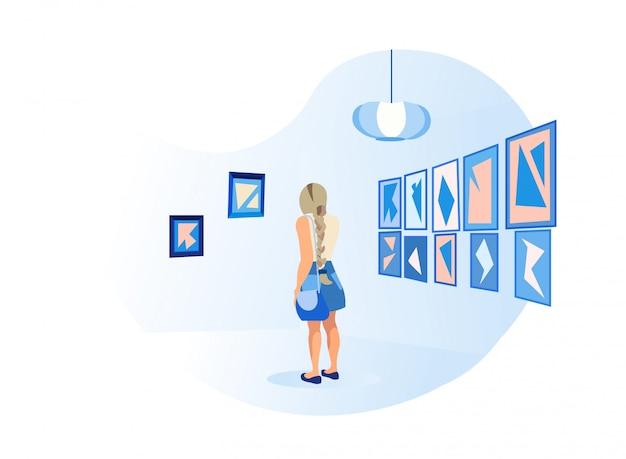 벽에 그림 앞에서 젊은 여자 스탠드
