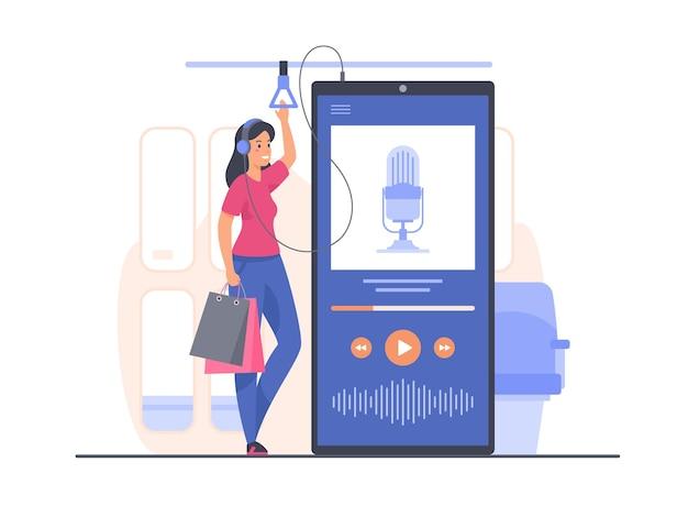 젊은 여성이 대중 교통에 서서 모바일 애플리케이션을 사용하여 팟 캐스트 녹음을 듣고 있습니다.