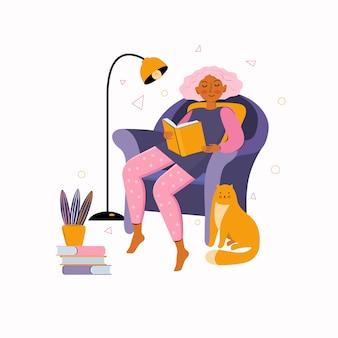 젊은 여자는 큰 안락의 자에서 책을 읽고 집에있어. 집에서 보내는 시간