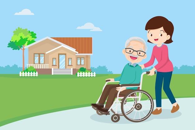 Молодая женщина гуляет с пожилым мужчиной в инвалидной коляске