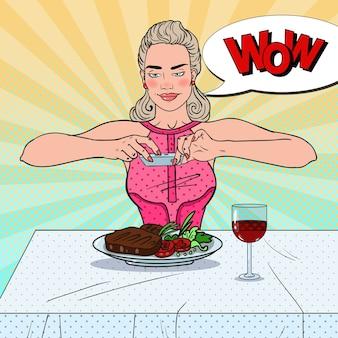 레스토랑에서 음식의 사진을 복용하는 젊은 여자
